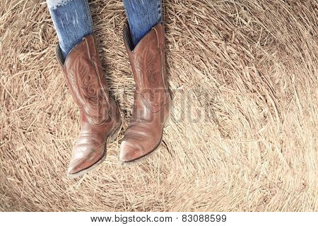 Western style image of cowgirl's legs in jeans and boots on dese