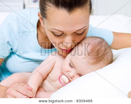 Happy Young Mother Near Sleeping Newborn