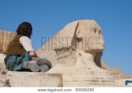 Man is sitting in front of Egyptian famous Sphinx in Giza