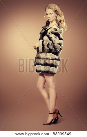 Fashion shot of a beautiful blonde woman wearing jewelry and fur coat. Studio shot. Full length portrait.