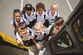 stock photo of cute  - Cute schoolchildren getting on school bus outside the elementary school - JPG