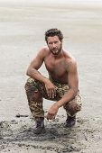 foto of shirtless  - Muscled Shirtless Soldier in Camouflage Pants and Black Shoes on the Beach Sand - JPG