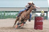 image of barrel racing  - Young woman barrel racing in a rodeo competition - JPG