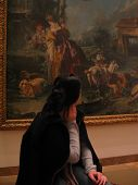 Woman Looking At Painting poster