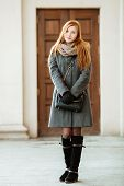image of redheaded  - Portrait of young beautiful redhead woman wearing coat and scarf posing outdoors with architectural background - JPG