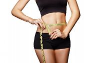 picture of outfits  - Fit and healthy young lady measuring her waist with a tape measure in centimeters and millimeters - JPG