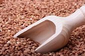 stock photo of deep-tissue  - Buckwheat groats with a wooden deep spoon for packaging - JPG