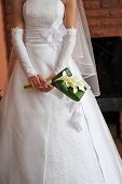 stock photo of debonair  - bride wearing wedding dress and holding bouquet - JPG