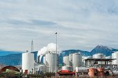 picture of italian alps  - Industrial plant of a furniture factory with smoking chimneys against the backdrop of the Italian Alps - JPG