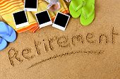 foto of retirement  - Beach background with towel flip flops blank photo prints and the word Retirement written in sand - JPG