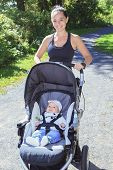 pic of buggy  - A Young mother jogging with a baby buggy - JPG