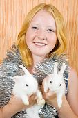 foto of tawdry  - Teen girl with two pet rabbits sitting in home - JPG