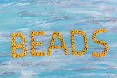 "picture of beads  - ""Beads"" text written in orange beads on a wooden background - JPG"