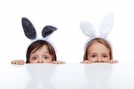 image of bunny rabbit  - Kids with bunny ears peeking from beneath the table  - JPG