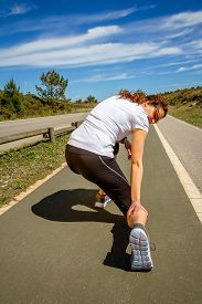 foto of calf  - Back view of athletic young woman with sportswear suffering pain in her leg calf by a muscle cramp on a training - JPG
