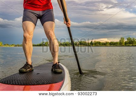 legs of muscular male paddler on a stand up paddleboard - a calm lake in summer