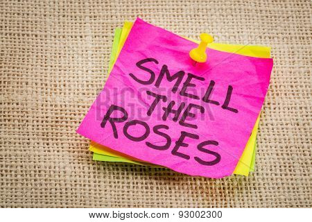 smell the roses - inspirational reminder on a sticky note against burlap canvas