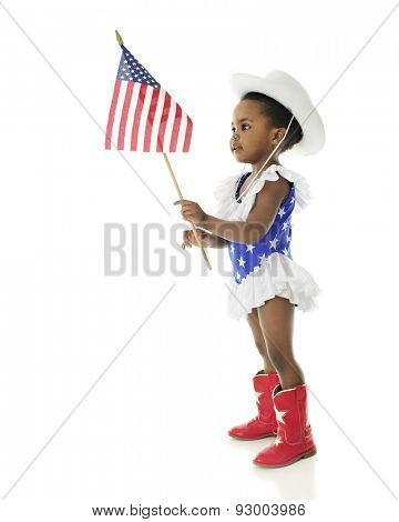 An adorable African American girl looking at the American flag she holds while wearing a red, white and blue majorette outfit.  On a white background.