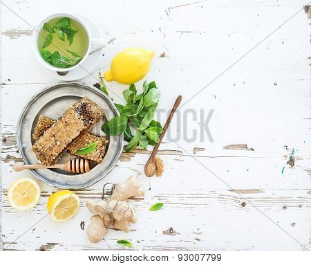 Cup of herbal tea with fresh mint, honey, lemon, ginger on rustic white wooden background. Top view