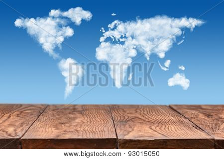 empty wooden table with world map made of white puffy clouds on sky as background