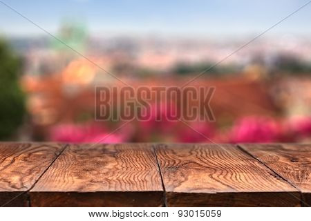 Empty wooden table with Prague on background with natural bokeh