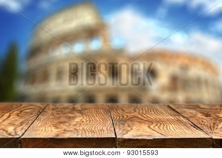 Empty wooden table with Colosseum in Rome on background with natural bokeh