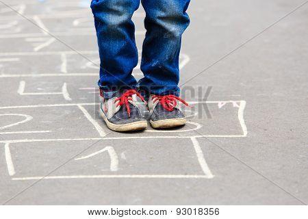 little boy playing hopscotch outdoors
