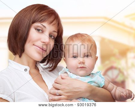 Portrait of a beautiful mother holding cute adorable baby, standing outdoor near their big new house, happy family life