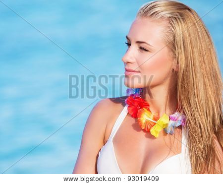 Portrait of cute blond female wearing beautiful Hawaiian leis, having fun on the beach, tropical party with traditional flowers garland on neck