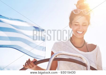 Portrait of beautiful happy woman driving sailboat, Greek flag on the deck, traveling along Mediterranean sea, active summer vacation