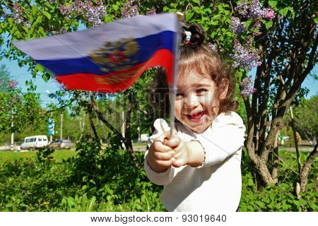 Little Girl Stands With Flag Of Russia In Front Of Lilac Bush On Sunny Day