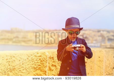 smart little boy taking photos while travel in Europe