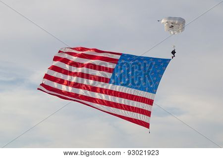 JACKSONVILLE BEACH, FL. USA - JUNE 6, 2015: A skydiver with a large US flag skydives onto Jacksonville Beach to open the Never Quit 5K Run.