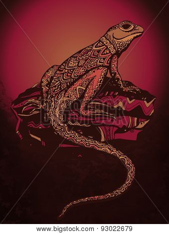 Ornate lizard with ethnic pattern. Rich colored reptile on a beautiful stone. Sunset background