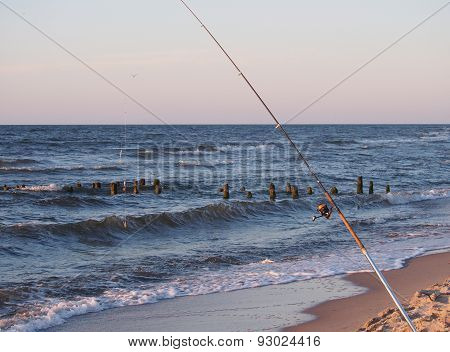 fishing-rod with and spinning-wheel on sea background