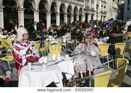 Tourists And Masked Persons In Colorful Costume Sitting In Cafe On San Marco Square, Venice