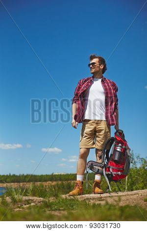 Young traveler with rucksack in natural environment