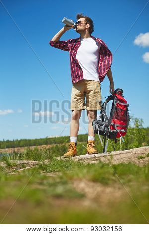 Young traveler with rucksack drinking water in natural environment