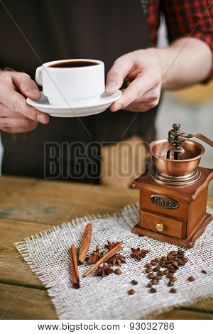Barista holding cup of black coffee over table with coffee grinder, coffee grains and aromatic flavorings