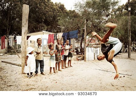 Boy jumping, making a salto in township, South Africa.