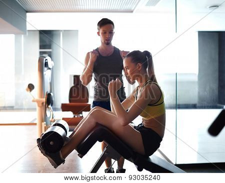 Active woman exercising on facilities while trainer helping her