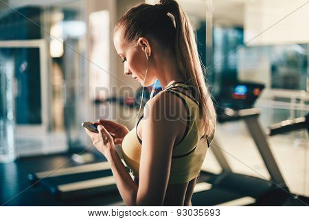 Active girl with smartphone listening to music in gym