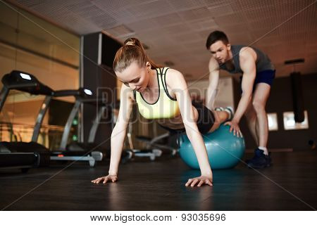 Girl in activewear doing push ups on ball with help of trainer