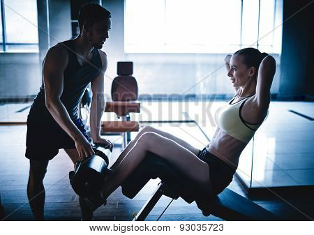 Active woman doing push ups in gym while trainer helping her