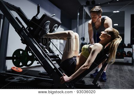 Fit woman doing exercise for legs on facilities with trainer near by