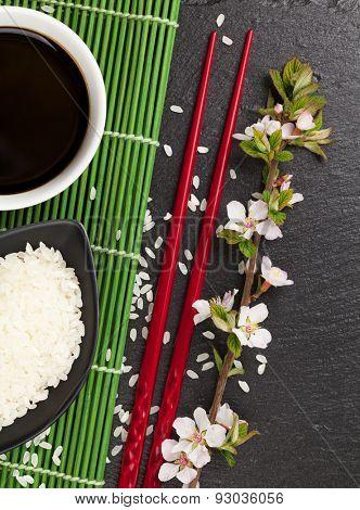 Japanese sushi chopsticks, soy sauce bowl, rice and sakura blossom on black stone background
