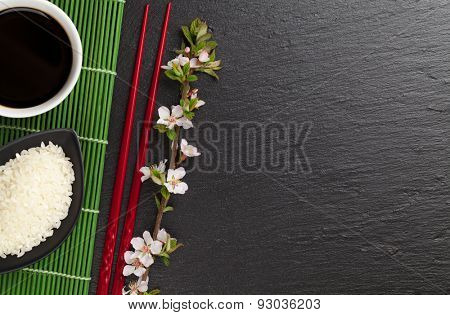 Japanese sushi chopsticks, soy sauce bowl, rice and sakura blossom on black stone background. Top view with copy space