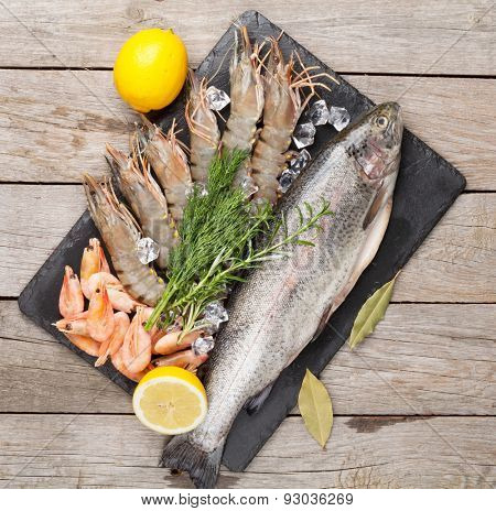Fresh raw sea food with spices on stone plate over wooden table background. Top view