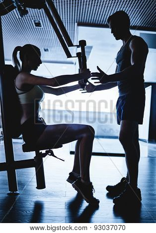 Trainer helping young woman to exercise on facilities
