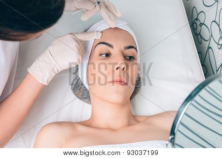 Female doctor showing to patient the face zones for a treatment